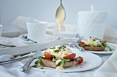 Eggs benedict with hollandaise sauce, rocket, and tomatoes on toast