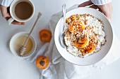 Porridge with apricots, almond butter, hazelnuts, honey, oatmeal, and cashew milk, served with coffee