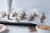 Piping chocolate meringues onto a tray