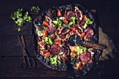 Schwarze Pizza mit Schinken, Wurst, Speck und Gemüse auf Holzuntergrund