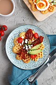 Hearty curry and cheese waffles with bacon and avocado, served with a cup of coffee
