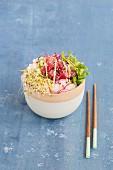 Poke Bowl mit Thunfisch, Sushireis, Radieschen, Gurkenscheiben und Sprossen