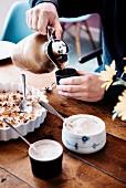 Apfelkuchen mit Sahne, im Hintergrund giesst Person Kaffee in Becher