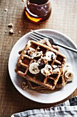 Wholemeal waffles with bananas, peanut butter, and syrup