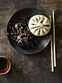 An Asian bao bun and squid ink noodles (Asia)