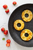 Griddled pineapple rings in a pan