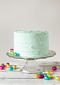 A pastel green buttercream layered cake with foil-wrapped mini chocolate eggs