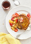 Vegan French toast with griddled pineapple, strawberries, coconut flakes and maple syrup