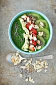 Smoothie Bowl mit Spinat, Kiwi, Erdbeeren, Apfel und Mandelblättchen