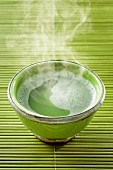 A steaming bowl of matcha tea
