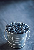 A small metal bucket of freshly picked blueberries