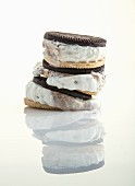A stack of ice cream sandwiches melting and reflected on a shiny white surface