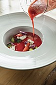 Strawberry gazpacho being poured into a soup bowl