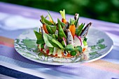 A vegetable tart with sardines on a table outdoors