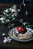 Crema di Balsamico fliesst auf Erdbeer-Pavlova dekoriert mit Obstblüten