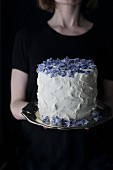 A woman serving a mascarpone cream cake with candied violets
