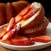 Bundt Cake with sliced strawberries and powdered sugar