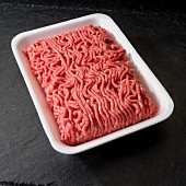 Ground beef in white tray on black background