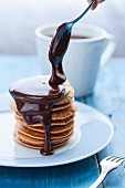 Chocolate sauce dripping off a spoon over a stack of pancakes