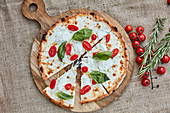 A pizza with buffalo mozzarella, cherry tomatoes and basil