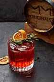 A cocktail with rosemary and dried orange slices