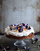A springtime cake topped with cream and pansies