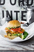 A crispy chicken burger with guacamole, shrimps, pineapple salsa and tomato slices