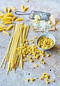 Various types of pasta next to parmesan