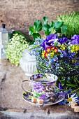 Eine Tasse Kaffee und Drahtkorb mit Wiesenblumen