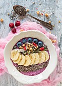 Berry smoothie bowl with bananas, chia, almonds and pumpkin seeds