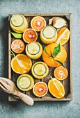 Healthy yellow smoothie with citrus fruit and ginger in bottles in wooden tray over grey concrete background