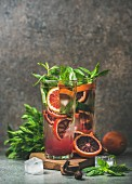 Blood orange citrus lemonade with mint and ice in tall glasses