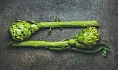 Fresh raw green artichockes over dark brown stone background