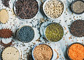 Various raw uncooked grains, beans, cereals in bowls and cups for healthy cooking over grey marble background