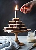 Brennende Kerze auf pyramidenförmig gestapelten glutenfreien Brownies
