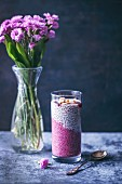 Beetroot juice chia pudding in a glass topped with cherry jam and chopped Brazil nuts