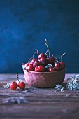 Fresh cherries in a ceramic bowl on a rustic wooden table