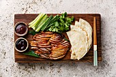 Peking Duck served with fresh cucumber, green onions, cilantro and roasted wheaten chinese pancakes
