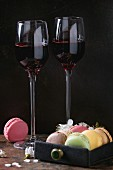 Two glasses of port wine with variety of colorful french sweet dessert macaroons with different fillings