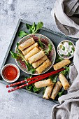 Fried spring rolls with red and white sauces, served in china plate on wood tray with fresh green salad and wooden chopsticks over gray blue texture background