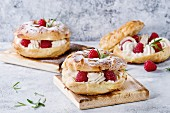 Homemade choux pastry cake Paris Brest with raspberries, almond, sugar powder and rosemary, served on wooden serving board