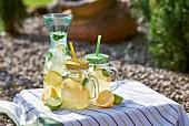 Hausgemachter Zitronensirup mit Minze, Eiswürfeln und Limettenscheiben