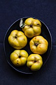 Several quinces in a black bowl