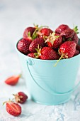 Fresh strawberries in a small metal bucket
