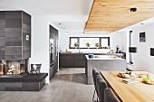 Puristische, offene Küche mit abgehängter Decke aus Altholz