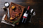 Grilled sliced Steak Striploin with Pepper sauce and bottle of Red wine on wooden background
