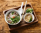 Pho Bo vietnamese Soup with beef and Soybean seedlings in wooden tray on wooden background
