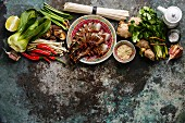 Ingredients for cooking Asian food with Tiger shrimps, udon noodles, mushrooms, greens, vegetables, spices on metal background