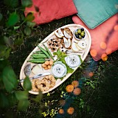 A fruit, nut and cheese selection board on a picnic