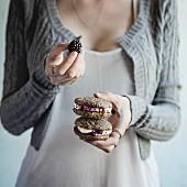 Frau hält selbstgebackene Sandwich-Cookies mit Brombeeren und Frischkäse in den Händen